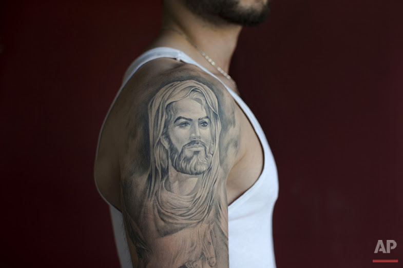 In this Tuesday, May 31, 2016 photo, Ali, 22, poses for a photo showing off his tattoo of Shiite Muslims' first Imam Ali, in the southern suburb of Beirut. (AP Photo/Hassan Ammar)