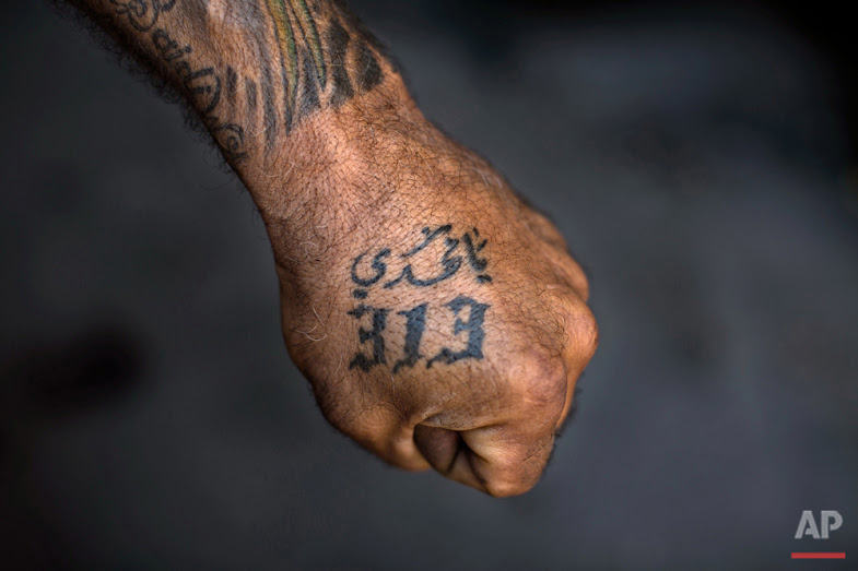 "In this Tuesday, May 10, 2016 photo, Ali Hussein Nasreddine, 50, poses for a photo showing off his tattoos with Shiite Muslim religious slogans in the southern suburb of Beirut. The tattoo in Arabic reads, ""Oh Mahdi, 313."" (AP Photo/Hassan Ammar)"