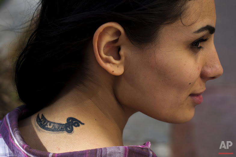 In this Wednesday, May 25, 2016 photo, Farah Najm, 21, an aviation maintenance student, poses for a photo showing her tattoo of the sword of Shiite Muslims' first Imam Ali, in Beirut. (AP Photo/Hassan Ammar)