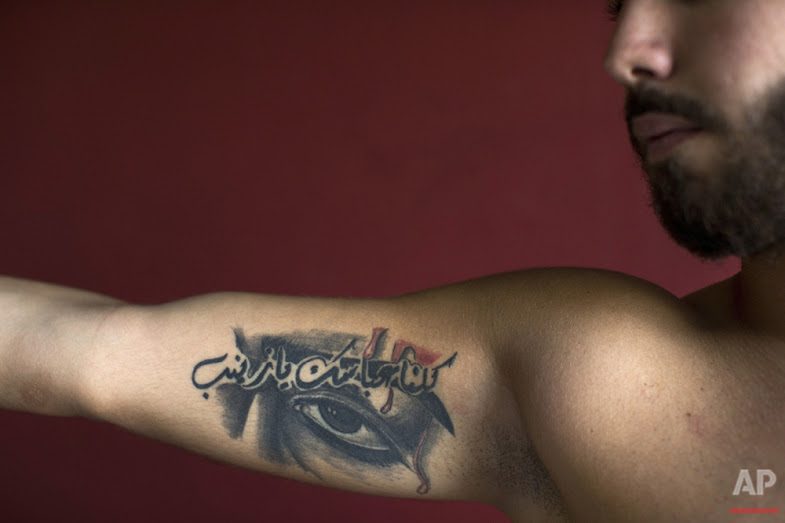 "In this Tuesday, May 31, 2016 photo, Abbas, 23, poses for a photo showing off his tattoos of Shiite Muslim religious slogans with Arabic that reads ""We are all your Abbas, oh Zeinab,"" in the southern suburb of Beirut. (AP Photo/Hassan Ammar)"