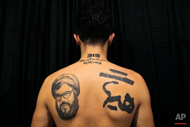 "In this Tuesday, July 19, 2016 photo, Hamza, 25, poses for a photo showing off his tattoos of Hezbollah leader Hassan Nasrallah and Shiite Muslim religious slogans in the southern suburb of Beirut. The tattoo in Arabic reads, ""It is impossible to humiliate us."" (AP Photo/Hassan Ammar)"