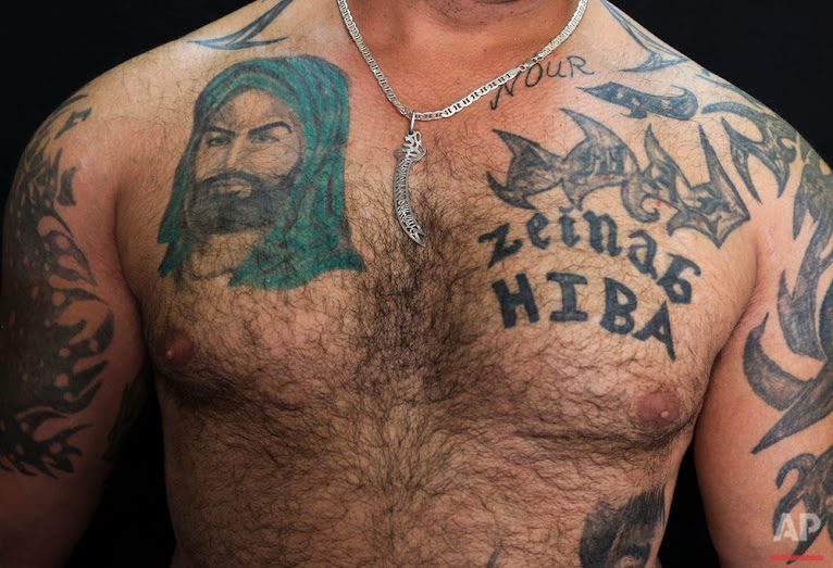 In this Tuesday, July 19, 2016 photo, Zulfiqar, 30, poses for a photo showing his tattoo of Shiite Muslims' first Imam Ali, left, in the southern suburb of Beirut. (AP Photo/Hassan Ammar)